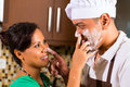 Asian couple baking chocolate cake in kitchen teasing each other while Royalty Free Stock Photos