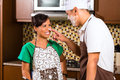 Asian couple baking chocolate cake in kitchen teasing each other while Royalty Free Stock Image