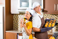 Asian couple baking muffins in home kitchen Stock Image