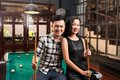 Asian couple in the bar young holding cues sitting on edge of pool table Royalty Free Stock Images