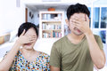 Asian couple cover faces at home covering their Stock Photography