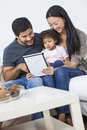 Asian couple family child using tablet computer a happy young men and women with young baby a at home Royalty Free Stock Images