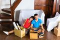 Asian couple having break while moving in real estate market young indonesian a home or apartment they are sitting on the floor Stock Photo