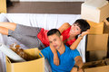 Asian couple having break while moving in real estate market young indonesian a home or apartment they are sitting on the sofa and Stock Photography