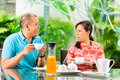 Asian couple having coffee on home porch the in front of their in the background a tropical garden Stock Photo