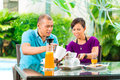 Asian couple having coffee on home porch the in front of their in the background a tropical garden Royalty Free Stock Image