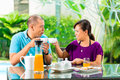 Asian couple having coffee on home porch the in front of their in the background a tropical garden Royalty Free Stock Photography