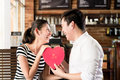 Asian couple having date in coffee shop with red heart Royalty Free Stock Photo
