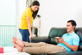 Asian couple having relationship difficulties young handsome with household tasks like vacuum and playing games on couch Royalty Free Stock Photo