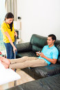 Asian couple having relationship difficulties young handsome with household tasks like vacuum and playing games on couch Royalty Free Stock Photography