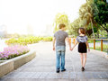 Asian couple holding hands walking in the park Royalty Free Stock Photo