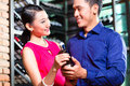 Asian couple holding wine bottle in restaurant portrait of a of Royalty Free Stock Photography