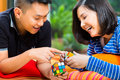 Asian couple at home playing with magic cube young indonesian men and women a Stock Photos