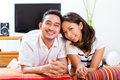 Asian couple at home in their living room young indonesian man and woman sitting on a couch it s weekend and they enjoying the Stock Photos