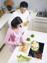 Asian couple in kitchen preparing meal together Royalty Free Stock Photos