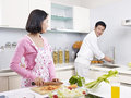 Asian couple in kitchen preparing meal together Stock Image