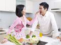 Asian couple in kitchen romantic preparing meal Stock Photos