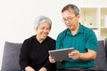 Asian couple looking at tablet together home Stock Photos