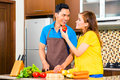 Asian couple preparing food in domestic kitchen cooking and cutting vegetables drinking red wine Stock Photo