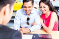 Asian couple signing sales contract for car at dealership Stock Photography