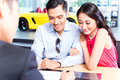 Asian couple signing sales contract for car at dealership Stock Images
