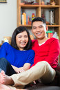 Asian couple on the sofa young indonesian men and women sitting at home a couch it s weekend and they enjoying leisure time Royalty Free Stock Photography