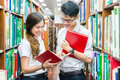 Asian couple of students in uniform at library Royalty Free Stock Photo