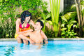 Asian couple swimming in resort pool hotel or club Stock Photography