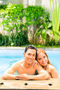 Asian couple swimming in resort pool hotel or club Royalty Free Stock Photo