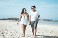 Asian couple walking on the beach of tropical Bali island, Indonesia. Royalty Free Stock Photo