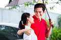 Asian couple walking with umbrella through rain Royalty Free Stock Photo