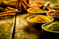 Asian cuisine with colourful spices a low angle view of bowls of focus to a bowl of turmeric based curry powder Stock Image