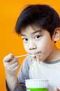 Asian cute boy with noodle cup young eating ramen noodles Stock Images