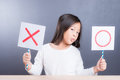 Asian cute girl  hold x accept and o refusing sign Royalty Free Stock Photo