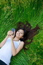 Asian cute girl texting on meadow Royalty Free Stock Photography