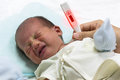 Asian cute new born baby check temperature with digital thermometer. Royalty Free Stock Photo