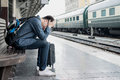 Asian depressed traveler waiting at train station after mistakes Royalty Free Stock Photo