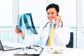 Asian doctor diagnosis radiograph in practise telephoning about x ray photograph his medical office Stock Image