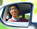 Asian driver is reflected in mirror smiling of car Royalty Free Stock Photo