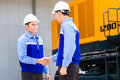 Asian engineers having agreement on construction site engineer handshake at machinery of or mining company Stock Photos