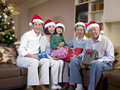 Asian family with christmas hats home portrait of an and gifts Royalty Free Stock Image