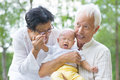 Asian family crying baby comforted by grandparents at outdoor garden Stock Photo
