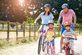 Asian family on cycle ride in countryside smiling at camera Stock Photo