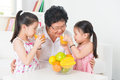 Asian family drinking fresh orange juice happy grandparent and grandchildren enjoying cup of squeeze fruit at home Stock Photos