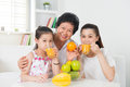Asian family drinking orange juice happy grandparent parent and grandchild enjoying cup of fresh squeeze fruit at home Royalty Free Stock Photography