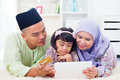 Asian family online shopping southeast using tablet pc computer with credit card at home muslim living lifestyle happy Stock Photos