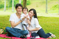 Asian family outdoor picnic happy activity parents and daughter having on garden green lawn Royalty Free Stock Image