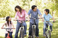Asian family riding bikes in park Stock Images