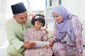 Asian family using tablet pc computer southeast at home muslim living lifestyle happy smiling malay parents and child Royalty Free Stock Photos