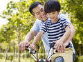 Asian father and son enjoying biking outdoors elementary age riding a bike in a park Stock Image